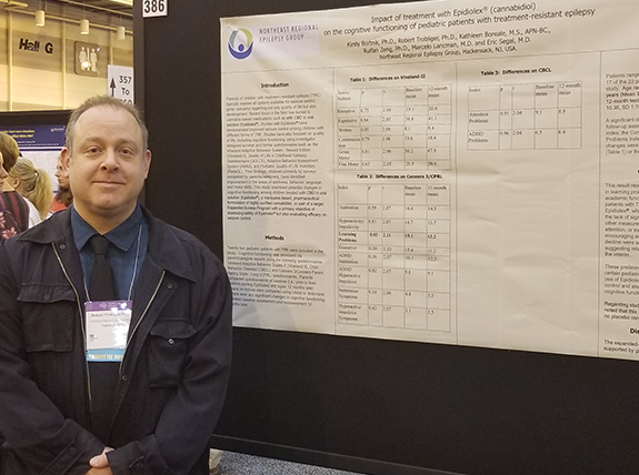 Dr. Robert Trobliger next to his poster on behavior and Epidiolex